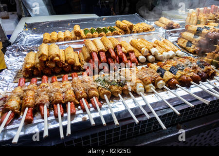 Street food on wooden sticks or skewers on a stall in Myeongdon in Seoul, South Korea. - Stock Image
