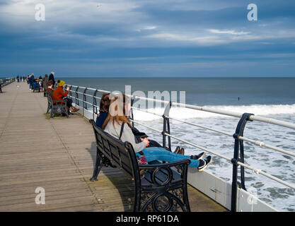 People sitting along Saltburn pier on an unseasonably warm February day in spring sunshine watching surfers and enjoying view south towards Huntcliff - Stock Image