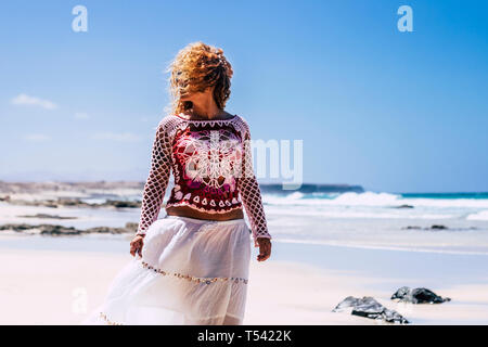 Beautiful hippy chic fashion female with long blonde curly hair outdoor enjoying the beach in summer vacation holiday - Nature in tropical place with  - Stock Image
