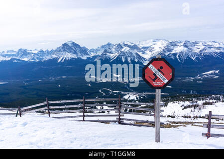 An avalanche danger warning sign prevents skiers from venturing into dangerous territory with the picturesque Canadian Rockies of Alberta in the backg - Stock Image