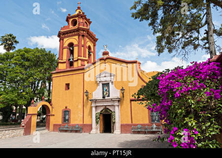 The Parroquia San Sebastian church with flowering Bougainvillea in the beautiful colonial village of Bernal, Queretaro, Mexico. Bernal is a quaint colonial town known for the Pena de Bernal, a giant monolith which dominates the tiny village is the third highest on the planet. - Stock Image