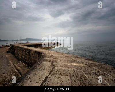 Dramatic skies over lovers holding hands along the Cobb in Lyme Regis, on the Jurassic Coast, Dorset, England - Stock Image