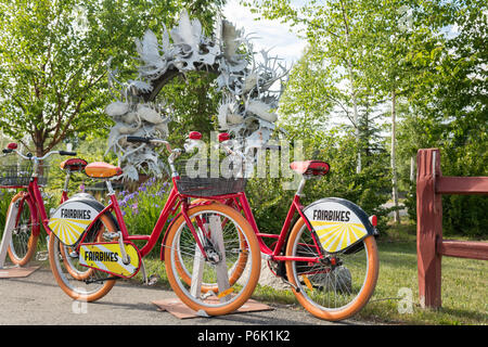Fairbikes bike share bicycles parked by the Moose Antler Arch in Griffin Park downtown Fairbanks, Alaska. The arch is made up of more than 100 moose and caribou antlers collected from all over Interior Alaska and is the world's farthest north antler arch. - Stock Image