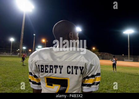 Young boy in football uniform watches team mates play on field at night time, Miami, Florida - Stock Image