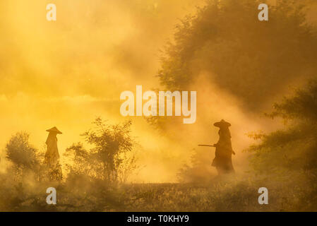 Two men are silhouetted on a dusty road in Bagan, Myanmar - Stock Image