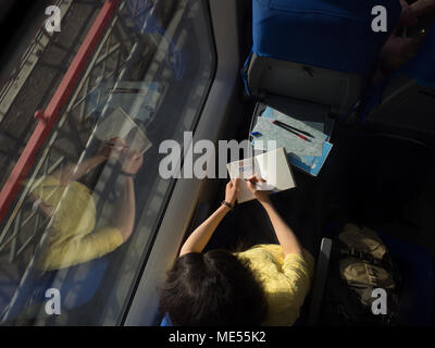 young woman loking in window with diary book and writing words travel blog train during traveling in train view from above - Stock Image