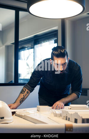 Architect looking at model building in office - Stock Image