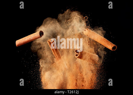 Food explosion with cinnamon sticks and powder, on black background. - Stock Image