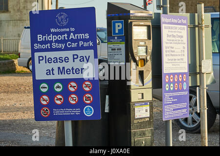 .Pay and Display car parking sign and ticket machine in West Bay, Dorset - Stock Image