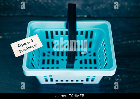 ecology and consumerism concept: spend better for less waste empty shopping basket with text - Stock Image
