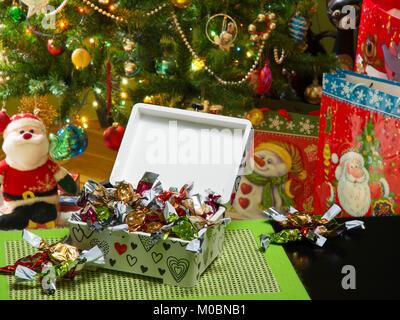Decoupage box full of traditional Hungarian parlour candies. A decorated Christmas tree, gift bags, and a Santa - Stock Image
