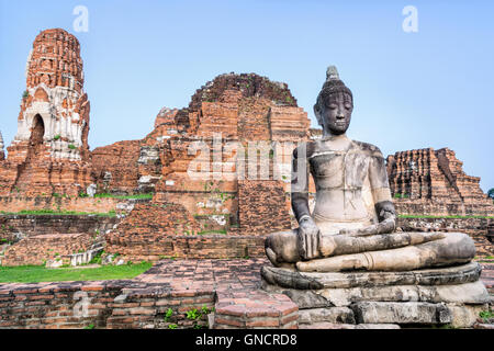 Ancient ruins of pagoda and old buddha statue at Wat Phra Mahathat temple is a famous attractions in Phra Nakhon - Stock Image