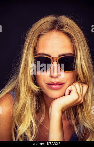 Young woman wearing sunglasses, portrait - Stock Image