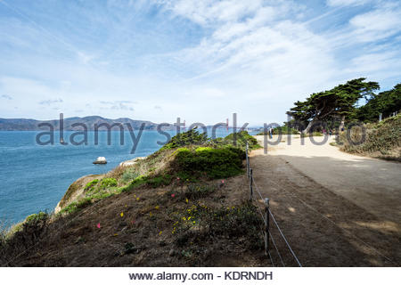 Tourists below USS San Francisco Memorial enjoy Eastern Coastal Trail and Overlook at Land's End, San Francisco, - Stock Image