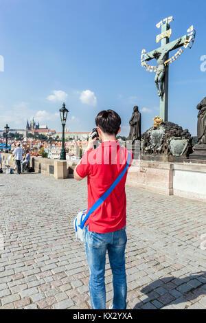 Young man taking photos on Charles Bridge Cross, Prague, Czech Republic - Stock Image