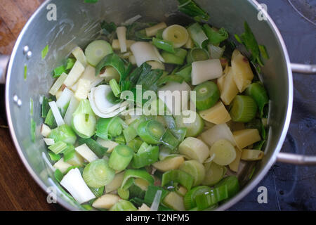 Potato and leeks cooking in a saucepan. - Stock Image