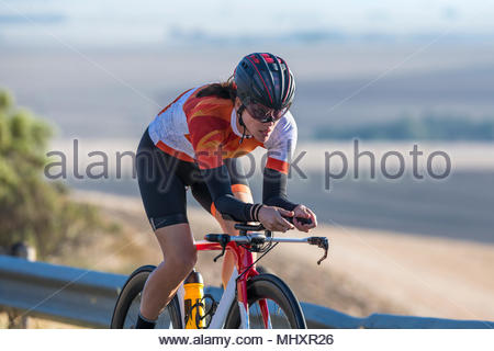 Female cyclist riding race bicycle on sunny open road - Stock Image