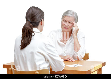 Female doctor with her senior patient with sleeping trouble, suffering of splitting headache or migraine, isolated on white background - Stock Image