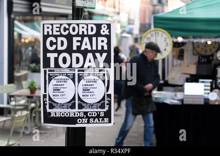 A flier on Winchester High Street advertising a record and CD fair, with a market stall and trader in the background - Stock Image