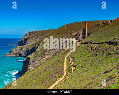 The South West Coast Path, winding its way over the Cornish cliffs and passing by the Towenroath Engine House, part of the Wheal Coates Mine, Cornwall - Stock Image