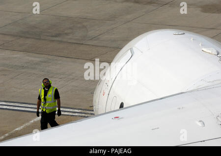 man wearing yellow high-viz tabard and ear-defenders standing by nose of Air France - CityJet BAE 146 Avro RJ-85 parked at London City - Stock Image