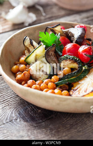 Healthy vegan bowl. Veggie salad with grilled vegetables cherry tomatoes, eggplant, zucchini, crispy crunchy roasted chickpeas in rural ceramic bowl o - Stock Image
