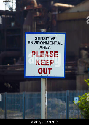 A warning sign for a Sensitive Environmental Area Please Keep Out   erected outside the now disused steel making blast furnace plant in Redcar  North  - Stock Image