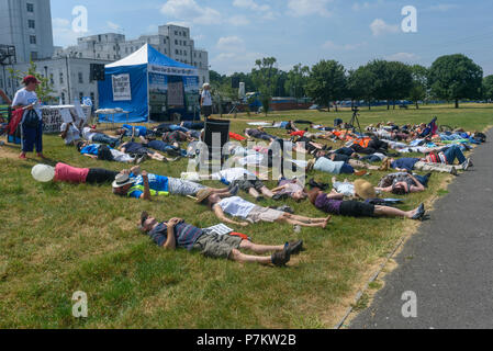London, UK. 7th July 2018.  People take part in a short i'die-in' at the end of the march by Keep Our St Helier Hospital (KOSHH) campaigners against the closure of acute facilities at Epsom and St Helier Hospitals in south Londonl. They had marched from Sutton to a rally there celebrating the 70th birthday of the NHS and opposing hospital closures. Credit: Peter Marshall/Alamy Live News - Stock Image