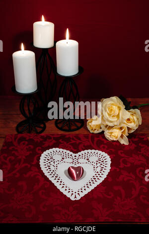 Heart shapped dollie and gemstone, three white candles in metal holoders and bouquet of yellow roses on wooden table. - Stock Image