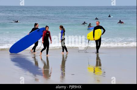 Young People carrying Surf boards,Sennen Cove,Cornwall,England,UK - Stock Image