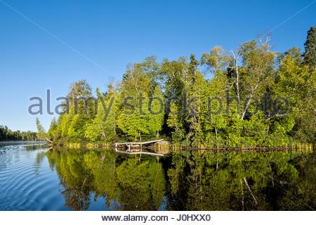 A boat dock reflects in Poplar Lake, northern Minnesota. - Stock Image