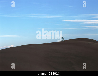 An unknown photographer waiting for his shot. Standing in the Great Sand Dunes National Park of Colorado's Rocky - Stock Image