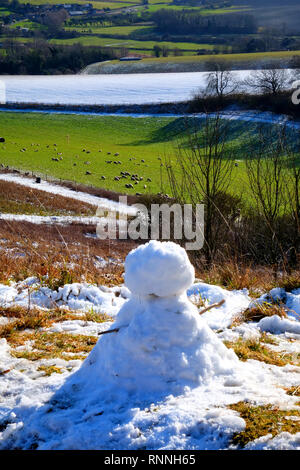 A small snowman with sticks as arms sits on the edge of snow covered rolling hills of the South Downs national park, East Sussex, UK, the village of G - Stock Image