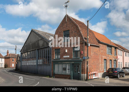 Bures village Suffolk UK, view of the old bus garage building and a dutch gabled house in Bures High Street, Suffolk, England, UK - Stock Image