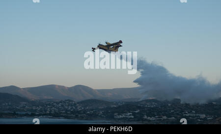 Fire emergency services spraying water preventing the fire from spreading further on the mountains. Saronida, East Attica, Greece, Europe. - Stock Image