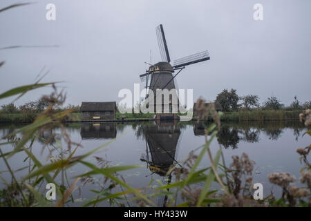 Traditional Windmill By Lake Against Sky - Stock Image