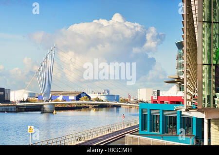 2 November 2018: Salford Quays, Manchester, UK - Media City Footbridge, and a large white cloud behind it. - Stock Image