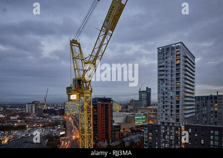 Manchester city centre skyline view across the rooftops from Salford 100 Greengate, crane working on foundations - Stock Image