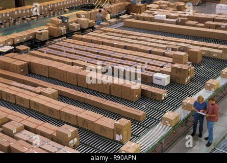 Overview of a large industrial distribution warehouse storing products in cardboard boxes on conveyor belts and racks. - Stock Image