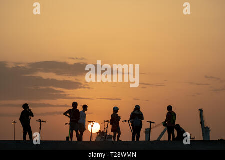 Silhouette of teenagers with their E-bikes during sunset - Stock Image