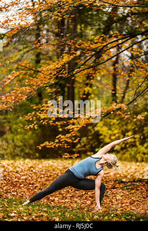 Woman practicing yoga in forest - Stock Image