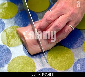 Female hands cutting raw chicken - Stock Image