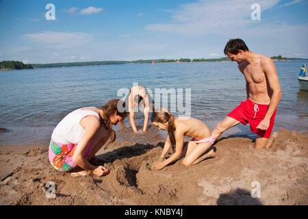 Family building sand castle, Swedish archipelago. - Stock Image