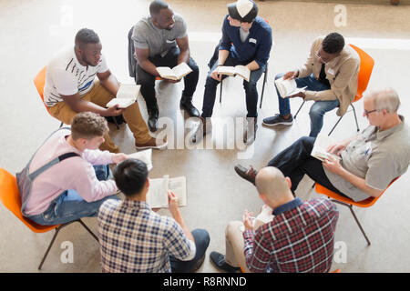 Men reading and discussing bible in prayer group circle - Stock Image