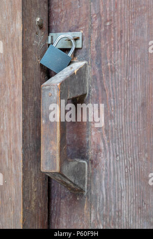 Closeup of a wooden aged latch and padlock - Stock Image
