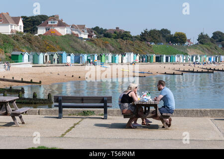 Young couple having a picnic and enjoying a sunny spring day by the beach at Hill Head in Hampshire, UK - Stock Image