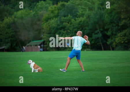 Handsome young man with english bulldog dog outdoors in city park forest. Man on a green grass with dog. Cynologist. - Stock Image