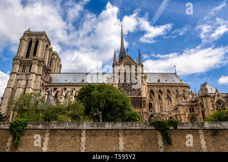 Famous Notre-Dame de Paris cathedral under beautiful blue sky with white clouds. - Stock Image