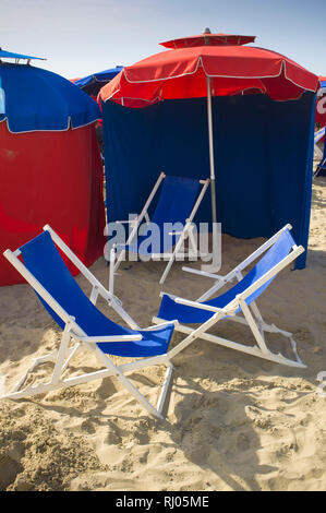 Colourful deck-chairs and sunshades on the beach at Deauville, Normandy, France. - Stock Image