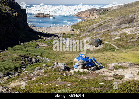 Painted stones marking blue trail hike to Holms Bakke approaching Ilulissat Icefjord or Kangia fjord with enormous - Stock Image